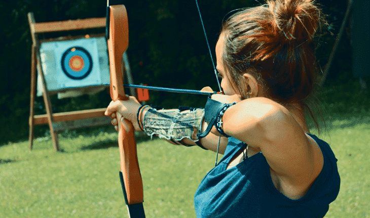 woman shooting composite bow longbow